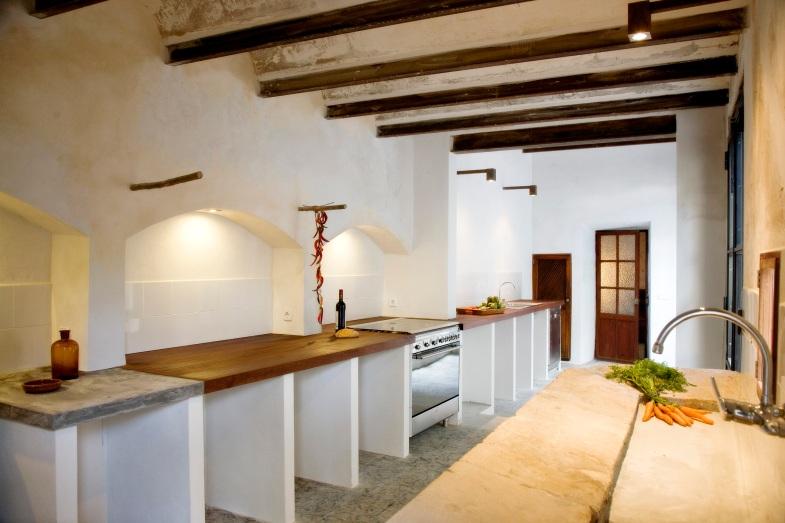 Köket med den långa köksbänken, spis, kyl, diskmaskin